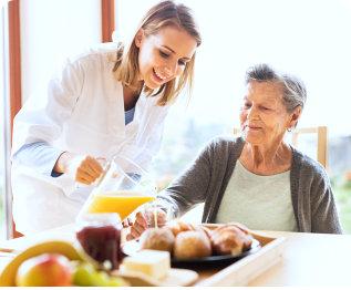 caregiver serving senior woman