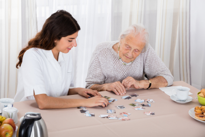 caregiver helping senior man on puzzle